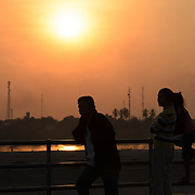 People rest against the railing of the walkway on the banks of the Mekong River as the sun sets. The land that can be seen in the distance is across the border in Thailand. Vientiane, Laos.