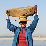 Woman carries and balances rocks on her head for a small salary. Smiling 1 very big rock and hat