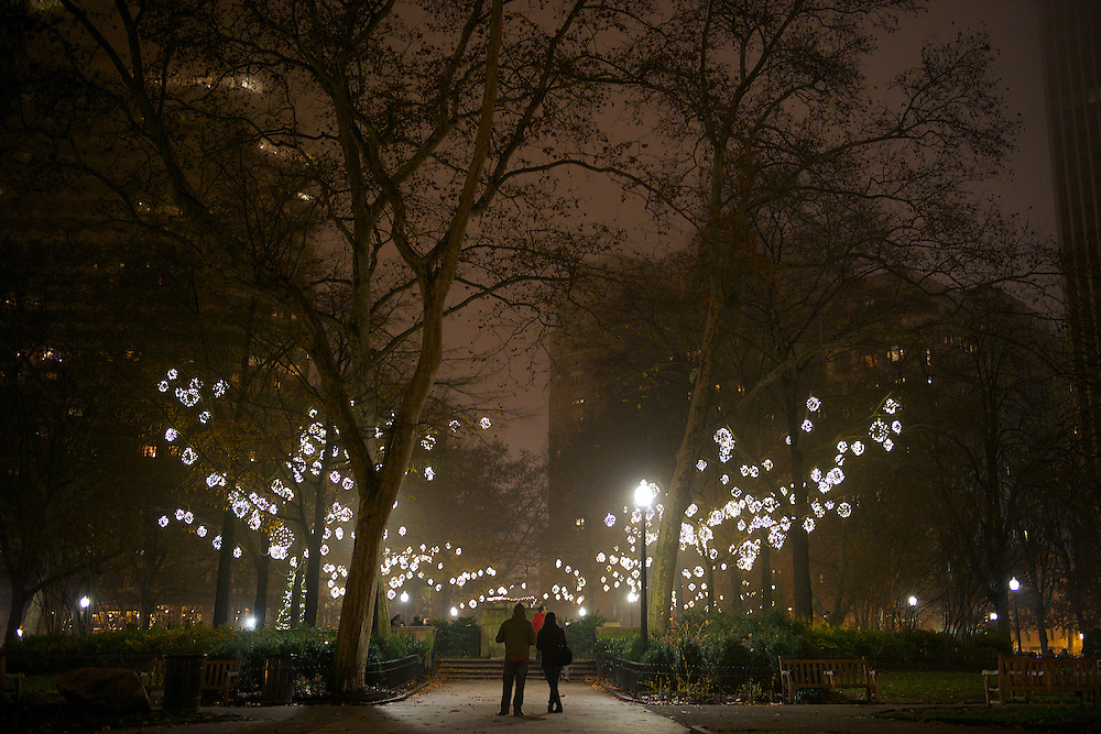 Pedestrians pause to admire Rittenhouse Square at night in Philadelphia.