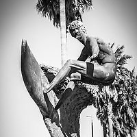 Huntington Beach surfer statue black and white picture. The bronze sculpture is named Ultimate Challenge by Edmund Shumpert. Huntington Beach is a beach city located in Orange County Southern California in the United States. Photo Copyright © 2012 Paul Velgos with All Rights Reserved.