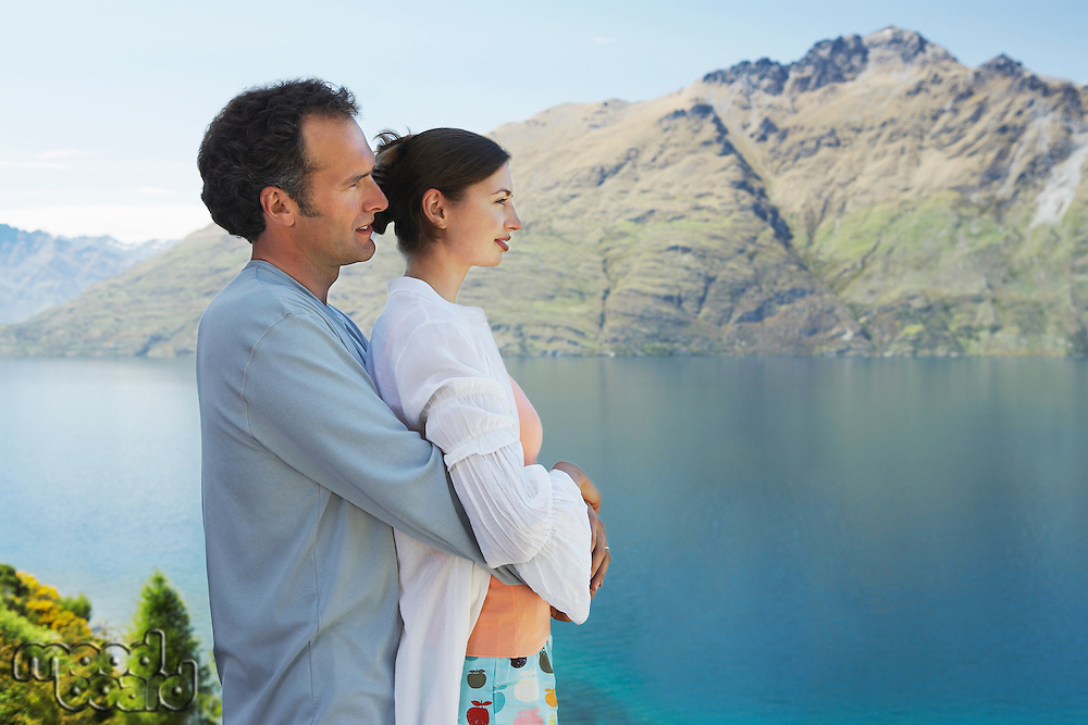 Couple embracing looking at mountain lake