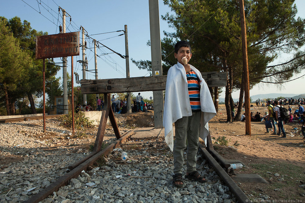 Refugee child eating an ice-cream on the train tracks near the border. <br /> Refugees arrive at Eidomeni border by bus and some times on foot. There they can cross to the republic of Macedonia on foot.