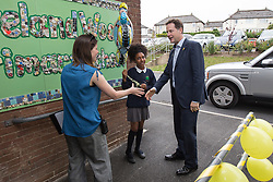 © Licensed to London News Pictures . 03/07/2014 . Leeds , UK . The Deputy Prime Minister , NICK CLEGG MP (right) , at Ireland Wood Primary School in Leeds today (Thursday 3rd July 2014) greeted by pupil Lashay Henry-Welsh (11) from Yeadon in Leeds (centre) . The Liberal Democrat leader and MP for Sheffield Hallam watches a Grand Depart school event with children taking part in cycling time trials and singing the the Tour de France anthem . Photo credit : Joel Goodman/LNP