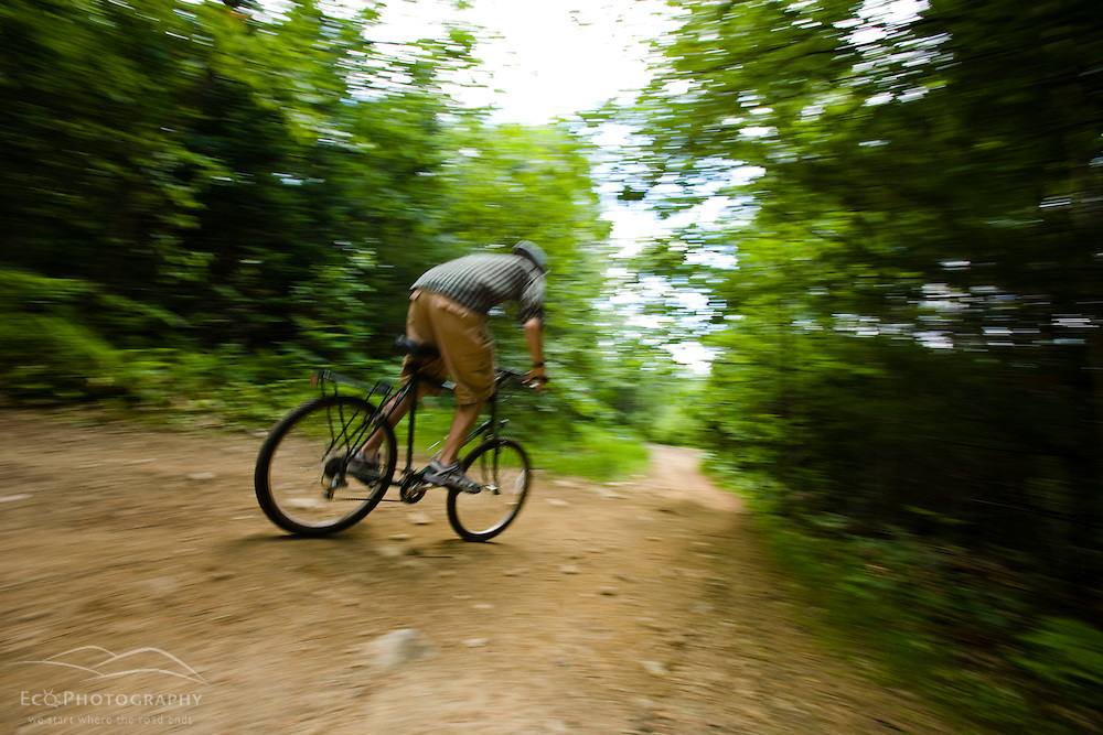 A man (age 19) mountain bikes on a trail in Turner, Maine.