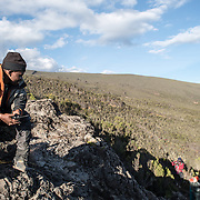 A Kilimanjaro guide sits on a rocky outcrop overlooking a valley on the Mweka Route.