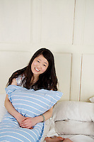 Cute young woman holding pillow