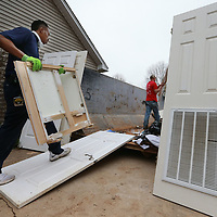 Hugh Foster of Service Master carries another section of kitchen cabinets to the dumpster as he and and other volunteers clean up a house that was flooded last week.