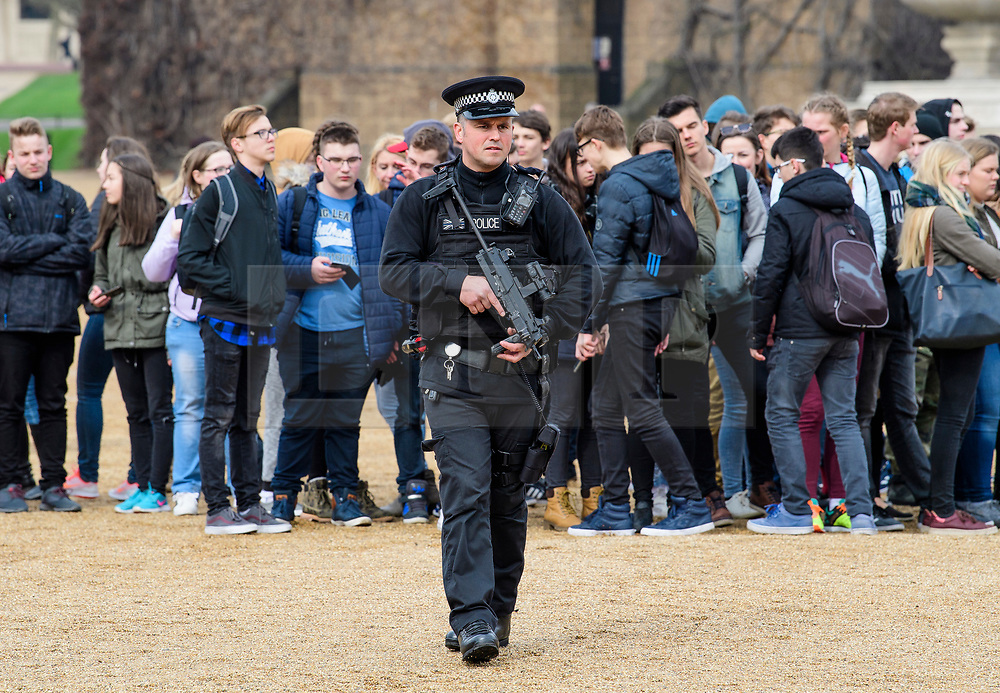 © Licensed to London News Pictures. 23/03/2017. London, UK. Armed police watch over tourists on horse guards during a guard changing ceremony, the day after a lone terrorist killed 4 people and injured several more, in an attack using a car and a knife. The attacker managed to gain entry to the grounds of the Houses of Parliament, killing one police officer. Photo credit: Ben Cawthra/LNP