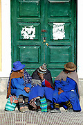 Three women chatting on a door step, Uyuni, Potosi, Bolivia