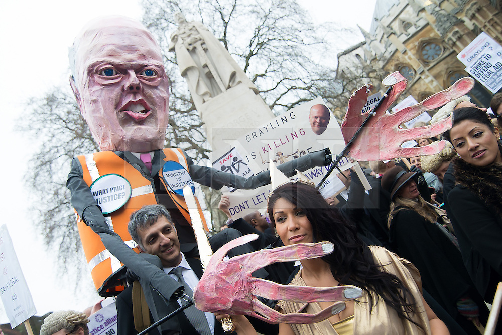 © Licensed to London News Pictures. 07/03/2014. Westminster, London, UK. An effigy of Justice Secretary Chris Grayling surrounds 'Lady Justice' at a Save UK Justice protest against government-proposed cuts to legal aid. Photo credit : David Tett/LNP