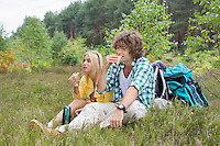 Hiking couple eating sandwiches while relaxing in field