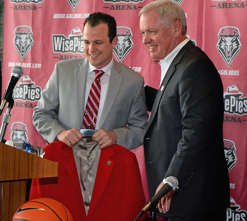 UNM's new men's basketball coach Paul Weir gets the cherry blazer from AD Paul Krebs.  Tuesday April 11, 2017. (Jim Thompson/Albuquerque Journal)