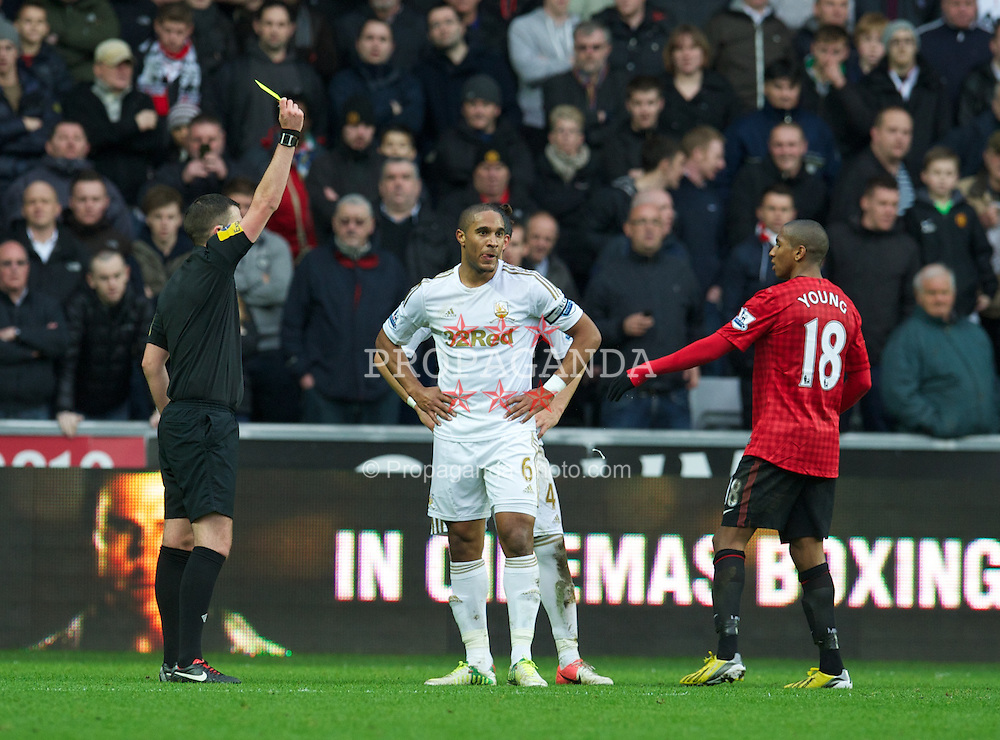 SWANSEA, WALES - Sunday, December 23, 2012: Swansea City's captain Ashley Williams is shown a yellow card by referee Michael Oliver during the Premiership match against Manchester United at the Liberty Stadium. (Pic by David Rawcliffe/Propaganda)