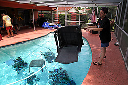 September 5, 2017 - Gulfport, Florida, U.S. - Jackie Kreuter, 56, (right) of Gulfport,tosses pool furniture in the pool so it doesn't fly around during the impending hurricane. Kreuter, along with her mother, husband, sister, daughter, grandson, five dogs and a bird are boarding up their home and business and leaving for Ocala to get out of Hurricane Irma's way. 'It's a mad dash to get everything done on time,' said Kreuter, a 20-year resident of Florida who was supposed to go on a Caribbean cruise this week. (Credit Image: © Tampa Bay Times via ZUMA Wire)