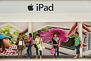 Commuters wait under an iPad advertisement Central District Hong Kong.