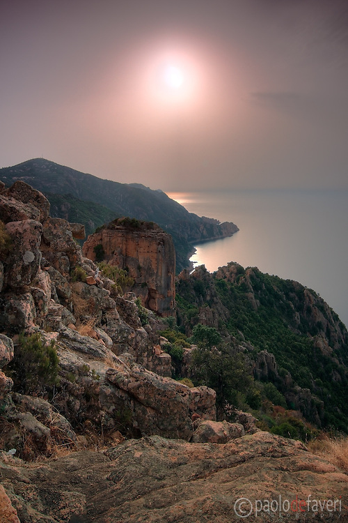 A hazy sunset over the amazing rock formations known as Les Calanches in the gulf of Porto, Corsica, France