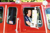 Male firefighter in moving fire truck
