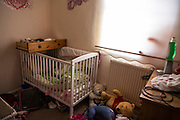 A draw sits on top of a babies cot in a bedroom of a council house on an estate in Leyland, Lancashire.