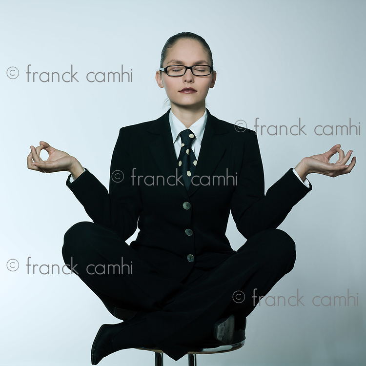 studio shot portrait of a beautiful young woman in a costume suit sitting on the lotus posture