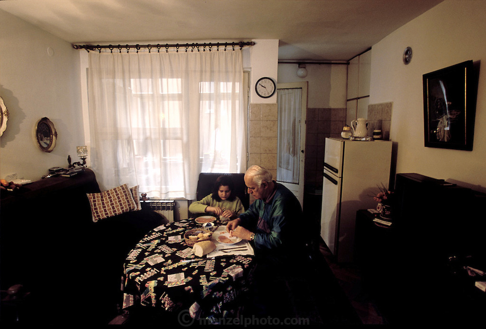 (MODEL RELEASED IMAGE). The Demirovic family of Sarajevo, Bosnia and Herzegovina, sits down to eat a breakfast of fried eggs, bread, and sliced cold meat. (Supporting image from the project Hungry Planet: What the World Eats.)