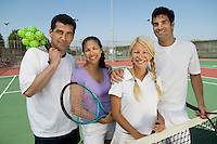 Four mixed doubles tennis players at net on tennis court portrait