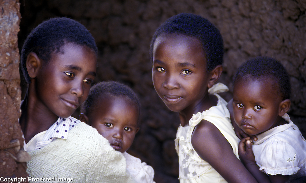 Young mothers pose with their children in an African village.