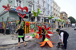 © Licensed to London News Pictures. 26/08/2018. London, UK. Last minute preparations are made to street decorations at family day of the 2018 Notting Hill Carnival. Up to 1 million people are expected to attend this weekend's event that is one of the worlds largest street festivals. Photo credit: Ben Cawthra/LNP
