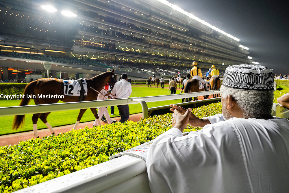 Man at parade ring at horse racing meeting at Al Meydan racecourse at night in Dubai United Arab Emirates