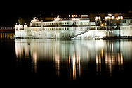 Lights from the Lake Palace Hotel reflected in Lake Pichola at night in Udaipur,<br /> Rajasthan, India