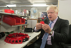 © Licensed to London News Pictures. 08/10/2014. Richmond, UK The Mayor of London, Boris Johnson, and Zac Goldsmith MP tour 'The Poppy Factory' in Richmond, Surrey, today 8th October 2014. Melanie Waters, the Chief Executive, briefed the Mayor and Zac Goldsmith on The Poppy Factory's 'Getting You Back to Work' initiative. To date, The Poppy Factory has supported nearly 500 wounded, injured or sick ex-service men and women back into the workplace through this new, nationwide initiative, through connections with commercial organisations like Transport for London. The goal is to help over 1,000 veterans by 2018. Employees at The Poppy Factory have made some 13 million poppies, 950,000 thousand remembrance crosses and 96,000 wreaths for The Royal British Legion Remembrance events in November. The Annual Field of Remembrance at Westminster Abbey is also planned and delivered by The Poppy Factory. Photo credit : Stephen Simpson/LNP