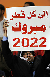 "A Syria fan holds up a sign saying ""Congratulations to the people of Qatar 2022"" for winning the bid to host the FIFA World Cup in 2022"