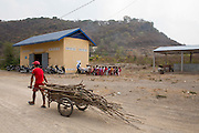 A man walks past carrying wood as VSO volunteer Giovanni Villafuerte delivers a workshop to around 40 farmers within the Banan co-operative outside their rice warehouse to help them increase their crop yields.  The VSO / Accenture IMA4P project, Banan, Cambodia.