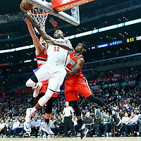12 December 2016: LA Clippers forward Luc Mbah a Moute (12) goes for the reverse layup past Portland Trail Blazers center Mason Plumlee (24) and Portland Trail Blazers forward Maurice Harkless (4) during the LA Clippers 121-120 victory over the Portland Trail Blazers, at the Staples Center, Los Angeles, California, USA.