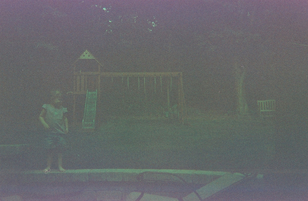 1. When was this photo taken?<br /> <br /> Summer 2005<br /> <br /> 2. Where was this photo taken?<br /> <br /> Pound Ridge, NY<br /> <br /> 3. Who took this photo?<br /> <br /> My 5 year old son<br /> <br /> 4. What are we looking at here?<br /> <br /> This is my daughter when she was two. She's standing on a patio wall we just installed. In the background was our children's play set<br /> <br /> 5. How does this old photo make you feel? <br /> <br /> Disappointed, as I often used to feel when picking up prints at the drugstore! Initially there's a feeling of anticipation dropping the film into the envelope &amp; sending it off!  When I'd pick up my photos two weeks later, they were never as good as I had hoped<br /> <br /> 6. Is this what you expected to see?<br /> <br /> I didn't know what to expect. This photo looks like it'd been improperly exposed, like when the back of the camera was opened before the film was fully rolled back. I didn't expect to see my daughter in the photo because we bought our first digital camera right before she was born &amp; I thought we stopped using our 35mm.<br /> <br /> 7. Does this photo bring back any memories?<br /> <br /> YES! Initially, when I received the old photos, I was so disappointed with the quality, that I didn't look closely at them. After a couple of months, I took a closer look, &amp; even bad photos, can evoke strong feelings &amp; memories. My children are teenagers now, &amp; the days of playing on the swing set have long past. What strikes me most in the picture, though, are my daughter's chubby bare feet! She hates walking outside in bare feet now!<br /> <br /> 8. How do you think others will respond to this photo? <br /> <br /> Because of the poor quality, I think others will barely give it a glance, as was my first inclination. But maybe they too will remember the frustration &amp; limitations of 110 &amp; 35mm film. Today, photos whose quality cannot be enhanced with software, or are not to our liking, are 