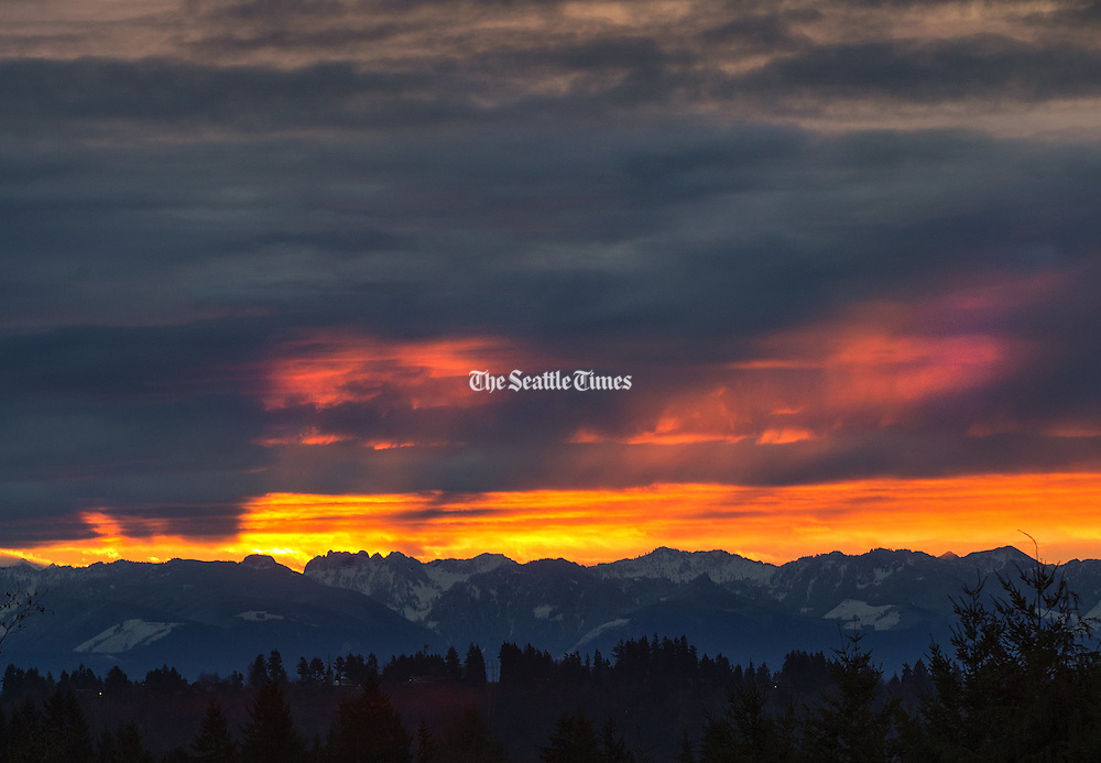 Early-morning light streams through dark clouds in this view of the Cascade Mountains during the sunrise. This view is from the Horizon View neighborhood near the Lake Forest Park reservoir. (Mike Siegel/The Seattle Times)