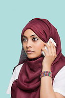 Young Muslim woman in maroon headcloth using cell phone against blue background