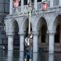 A tourist is being photographed in St Mark Square in front of Palazzo Ducale  during seasonal High Tide. A few days of exceptional high tides up to 120cm are expected during the next few days meaning 30% of Venice will be under water