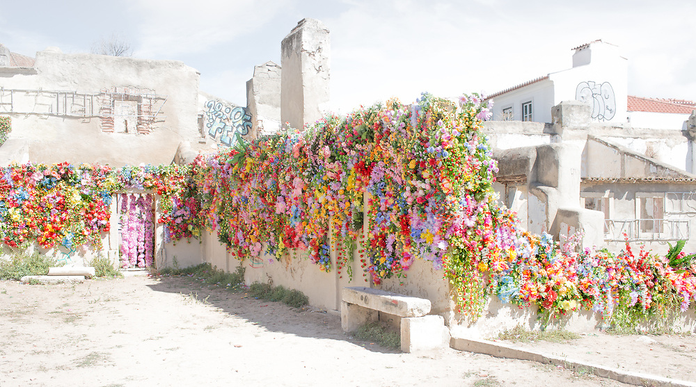 Hundreds of colourful plastic flowers, washed by midday sunlight, decorate a rundown building in the old part of Lisbon.
