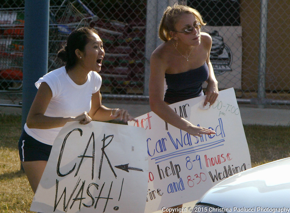 After the community heard about the dresses and food that was destroyed for her upcoming wedding, a local volunteer youth group sponsored a fundraising car wash to help Vee and her family with the wedding expenses.  Vee encourages a vehicle to stop for a wash.