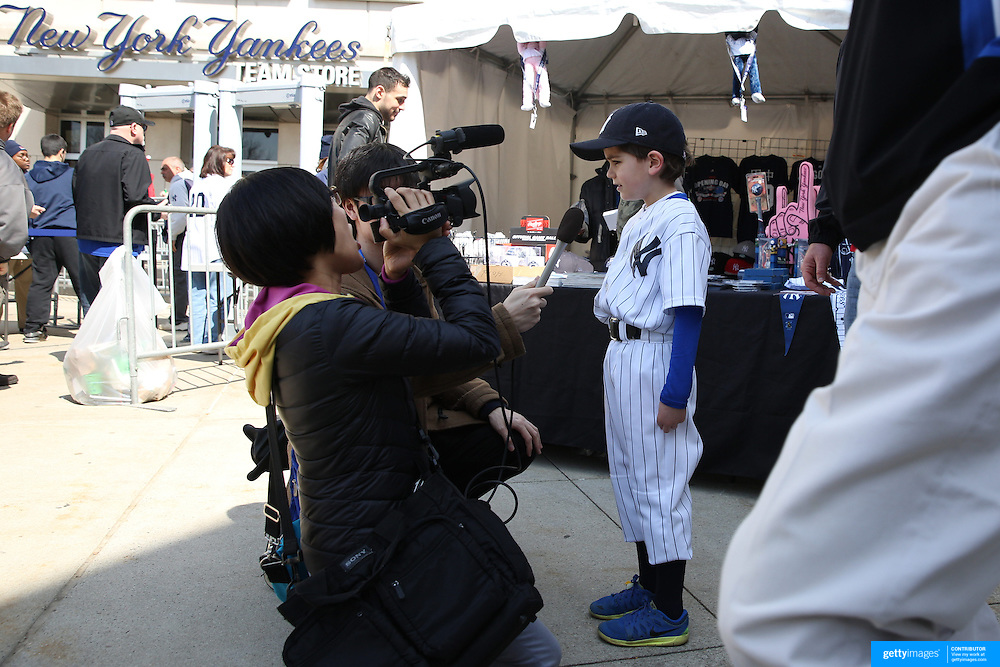 A Japanese film crew work interview a young fan outside Yankee Stadium before the New York Yankees Vs Toronto Blue Jays season opening day at Yankee Stadium, The Bronx, New York. 6th April 2015. Photo Tim Clayton