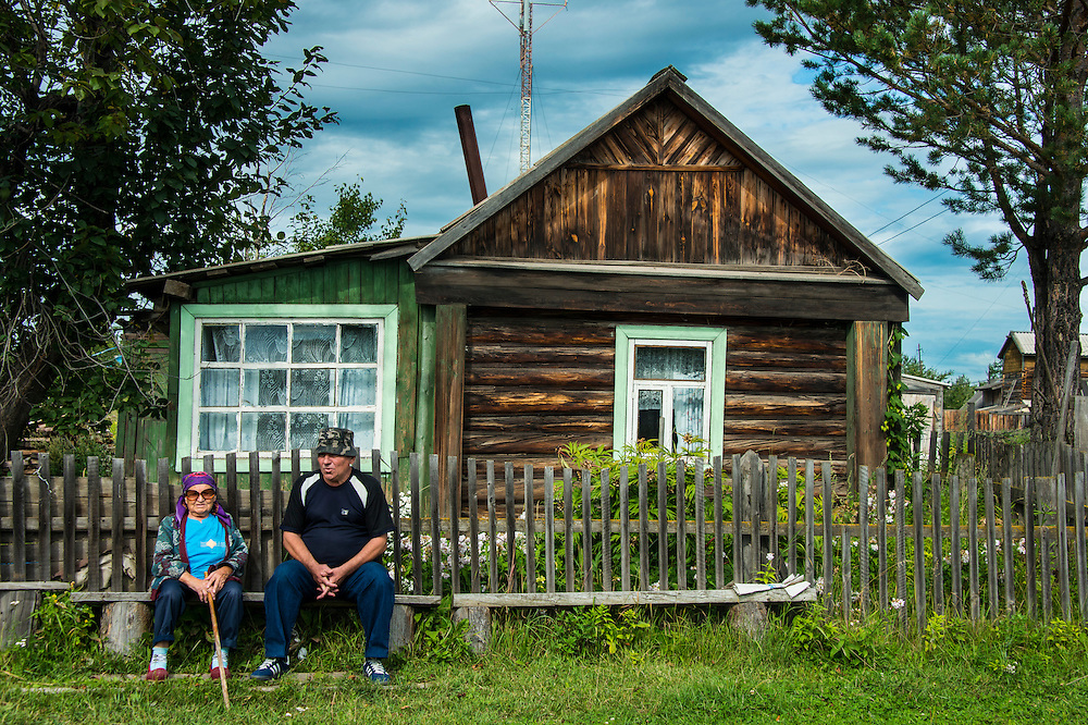 Old couple sitting on a bench before their wooden house below Tolbachik volcano, Kamchatka, Russia