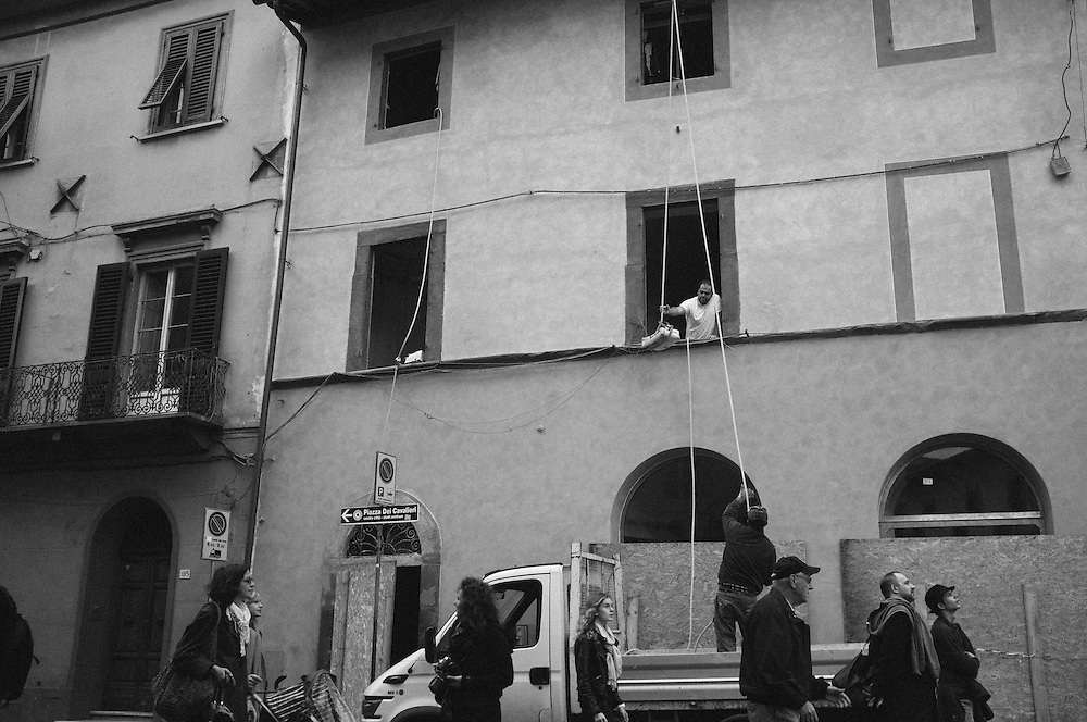 Builders hoisting up materials using ropes and pulleys in Pisa, Italy