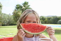 Portrait of girl (5-6) holding slice of watermelon