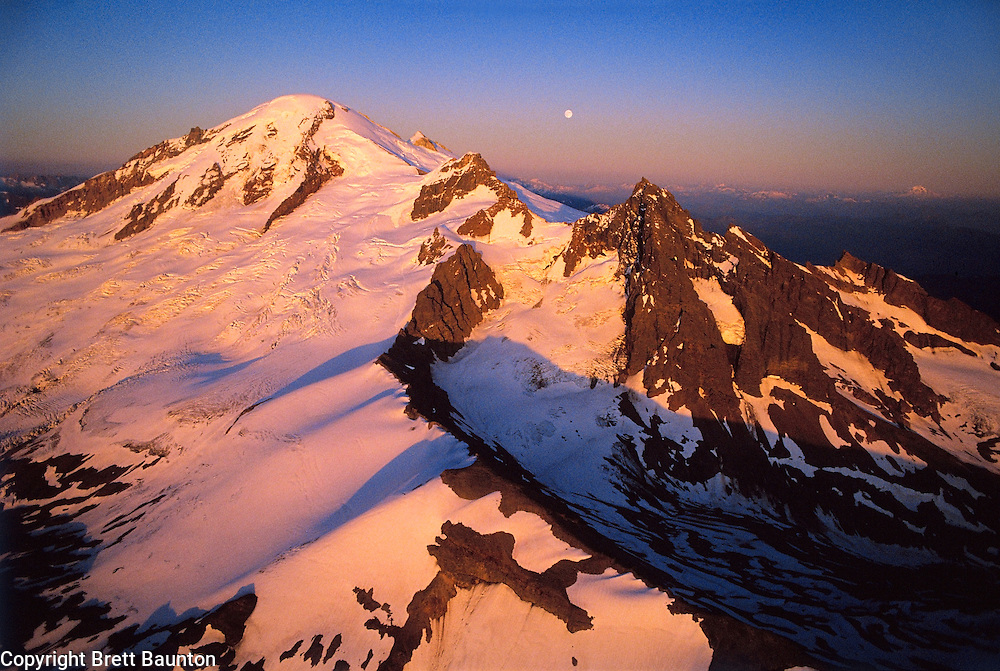 Mt. Baker aerial, WA, USA. 10,778 ft / 3285 m..Mt. Baker Wilderness Area. North Cascades..Black Buttes, Coleman and Roosevelt Glaciers..Climbers Route is just left of the center rock rib to the pass, then left up the  Roman Wall. Northwest Face..Moonrise and Sunset..Brett Baunton.