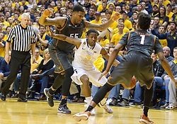 West Virginia Mountaineers guard Juwan Staten (3) weaves in between defenders against the Texas Longhorns during the second half at the WVU Coliseum.