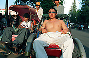 October 2004 - Phnom Penh; Cambodia - Chhin Toeun (left); 24; or Hawaii to his friends; sits in a rickshaw next to his friend Charlie; 32; to travel a few blocks across central Phnom Penh. After spending more than 7 years in prison; he was deported back to Cambodia. Previously a gang member in the US; he remains dressed like an American covered in tatoos and is seen as a foreigner to local Khmers even though he was born in Cambodia. After escaping the Khmer Rouge regime to the US as refugees; many young American Cambodians are being sent back to Cambodia never to return to the US again. A new policy in 2002 meant that any US-Cambodian who still had not applied for US citizenship and had been convicted of a felony would be deported back to Cambodia after living in the US all their life. Over 1; 400 convicted felons are proposed to be sent back in the next few years and naturally the re-adjustment to a life they don't know or understand is a difficult one. Photo Credit: Luke Duggleby