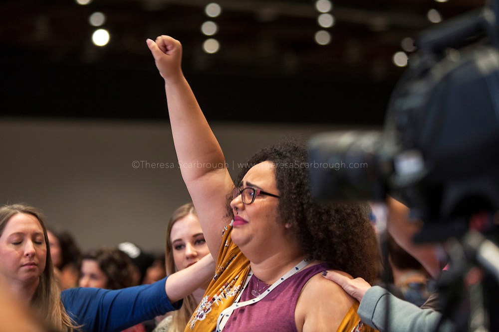 Odette Rodriguez (center) raises a fist in support of remarks of the devastation in Puerto Rico at the opening session of the Women's Convention at the Cobo Center, Detroit Michigan, Friday, October 27, 2017