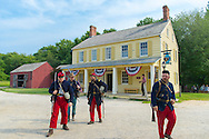 "Old Bethpage, New York, USA. August 30, 2015. American Civil War soldiers from the 14th Brooklyn Regiment (14th New York State Militia) AKA The Brooklyn Chasseurs, are portrayed in front of the yellow and white Noon Inn tavern during the Old Time Music Weekend at the Old Bethpage Village Restoration. During their historical reenactments, members of the non-profit 14th Brooklyn Company E wear accurate reproductions of ""The ""Red Legged Devils"" original Union army uniform."