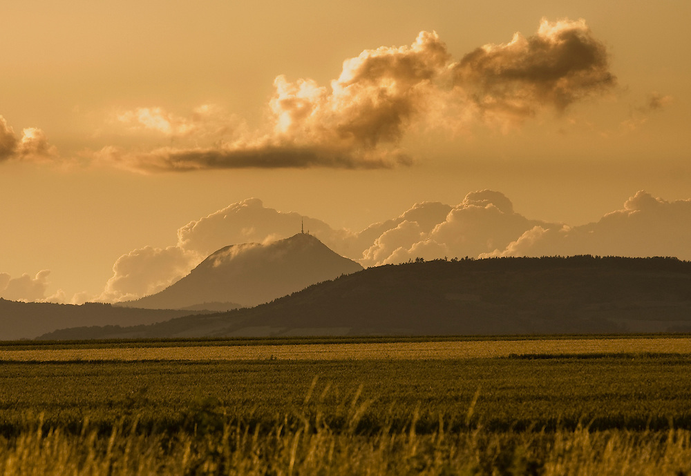 View on the Puy de Dôme in sunset with farmers field in the front.