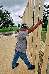 23 August 2013. Lower 9th Ward, New Orleans, Louisiana.<br /> Katrina 8 years later. In a tale of two cities, the hardest hit neighbourhoods struggle to revitalize and return. Rene Lagos, a contractor working for Brimmer Construction Services begin the extensive process of rebuilding a formerly derelict house. Many half finished or blighted properties and vacant overgrown lots remain dotted throughout the landscape. Residents who have returned complain of limited services, infrequent police patrols, high crime rates, rampant mosquitos and uncontrolled vermin. <br /> Photo; Charlie Varley